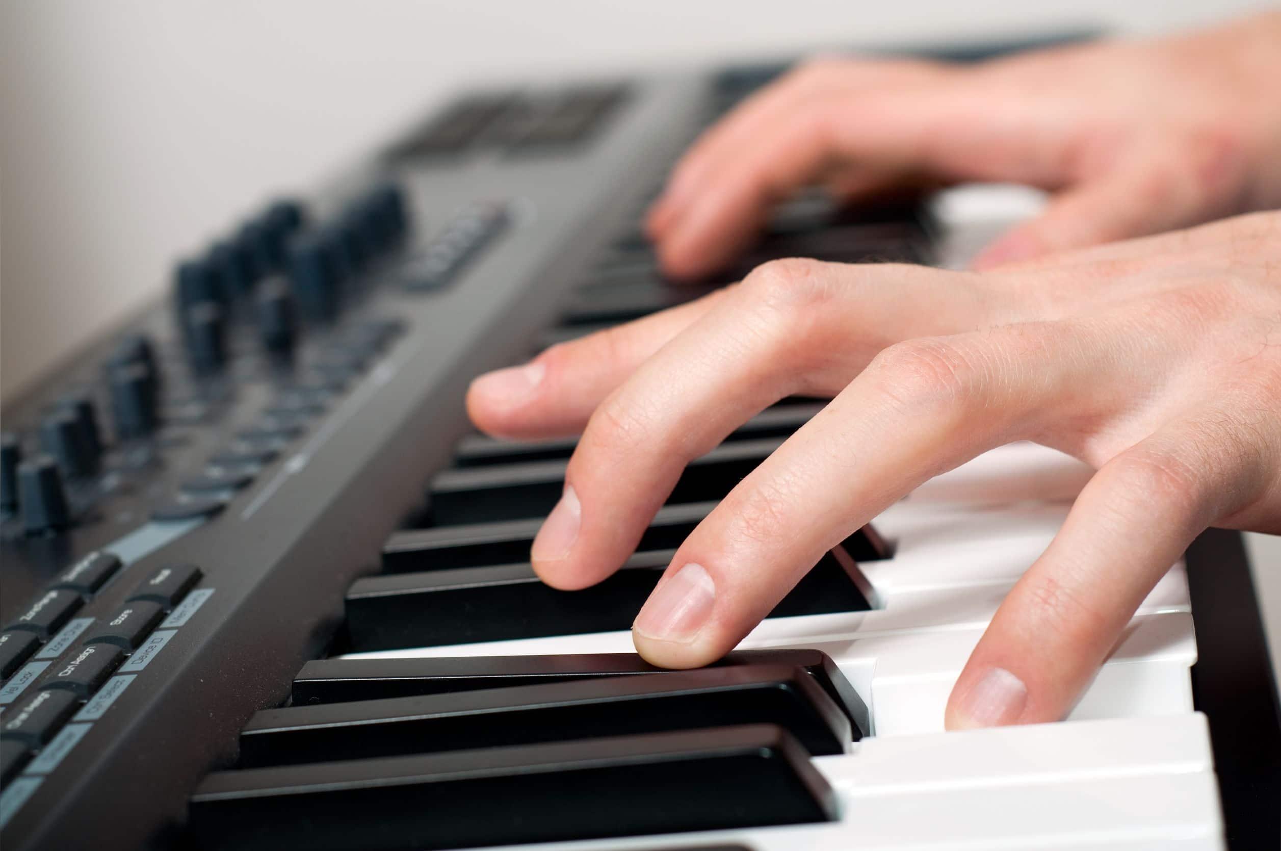 Close em mãos tocando teclado