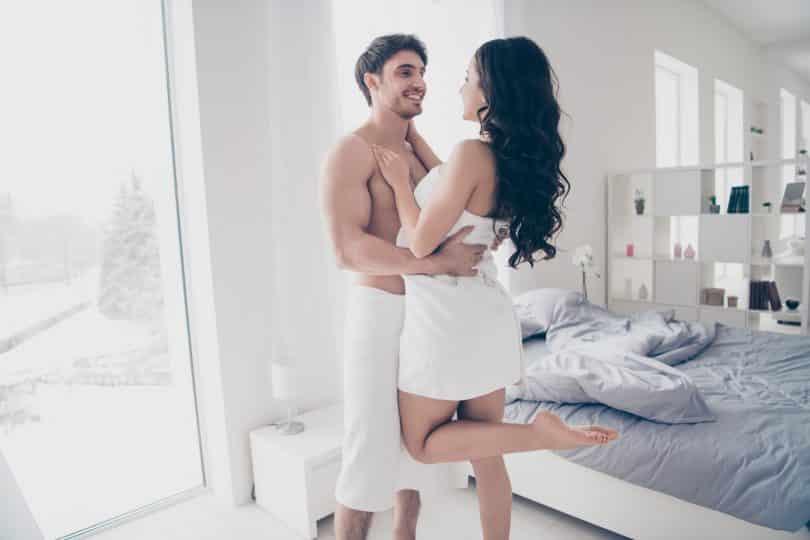 Homem e mulher abraçados com toalhas de banho cobrindo seus corpos.
