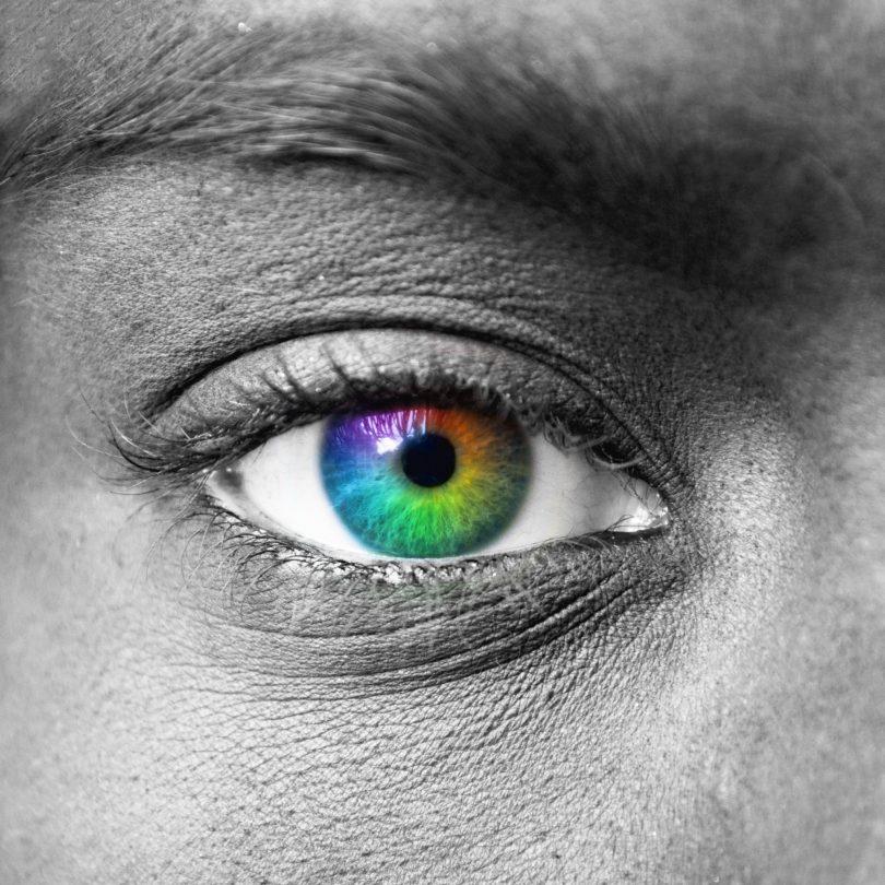 Foto preta e branca, próxima de olho humano, com a íris colorida com as cores do arco íris.
