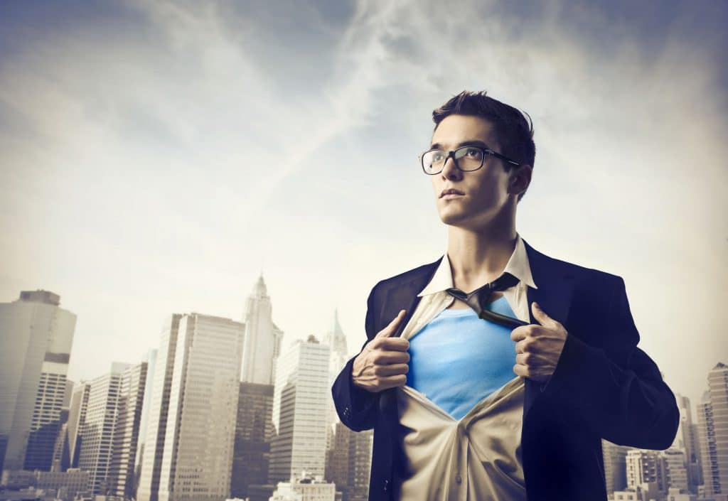 Homem abrindo a camisa do terno e embaixo está usando uma roupa de super-herói.
