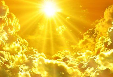 Nascer do sol, muito luminoso, cercado por nuvens brancas.