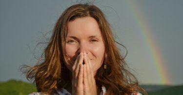 Mulher agradecendo. Com as mãos em sinal de oração. Fundo de arco-íris.