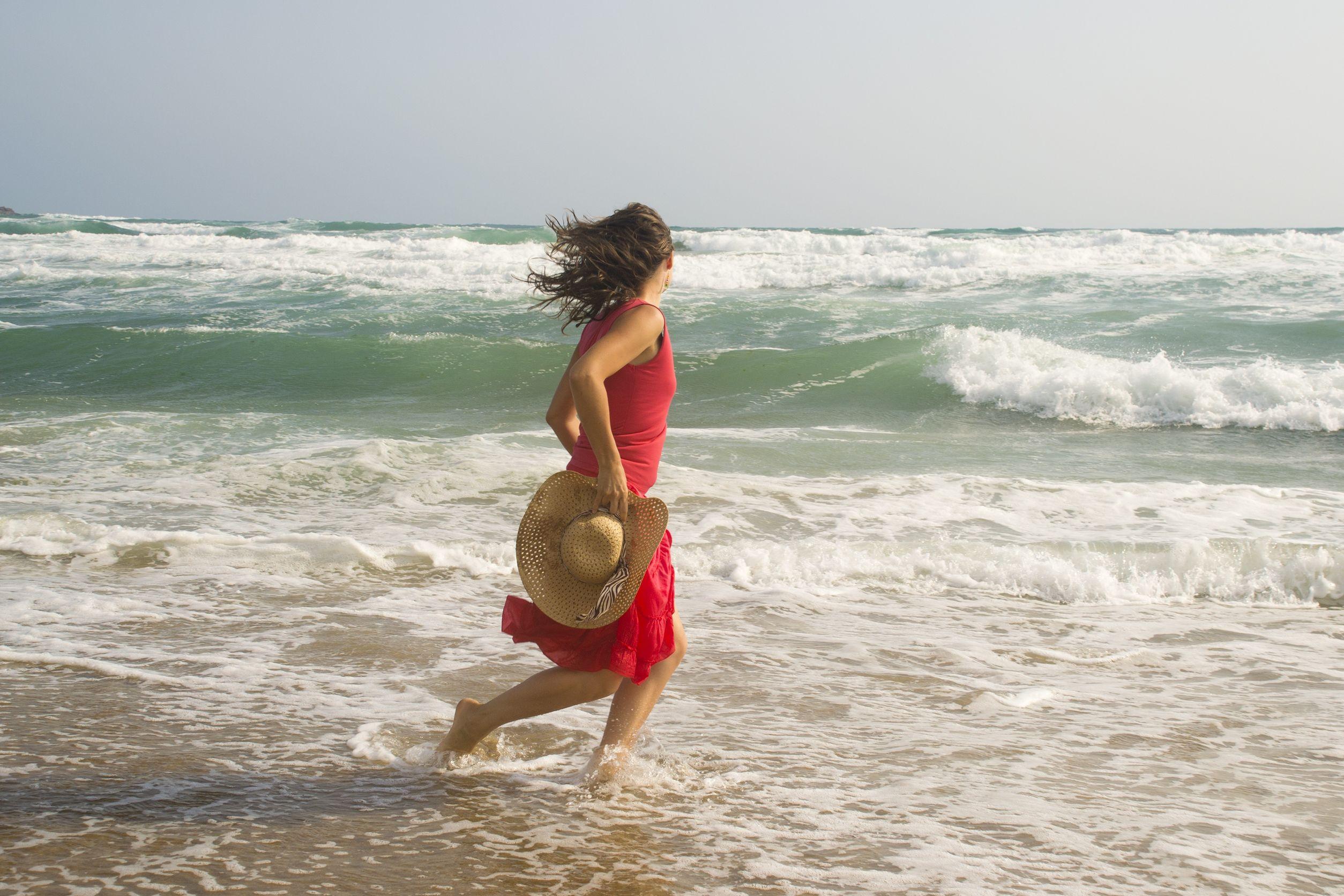Mulher correndo na beira do mar. Ela usa um vestido vermelho e segura um chapéu de palha na mão.