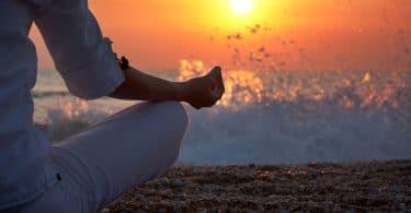 mulher praticando ioga perto do mar ao pôr do sol