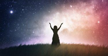 Silhueta de uma mulher com os braços estendidos para cima com uma galáxia ao fundo.