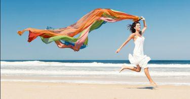garota na praia correndo e segurando um pedaço colorido de tecido