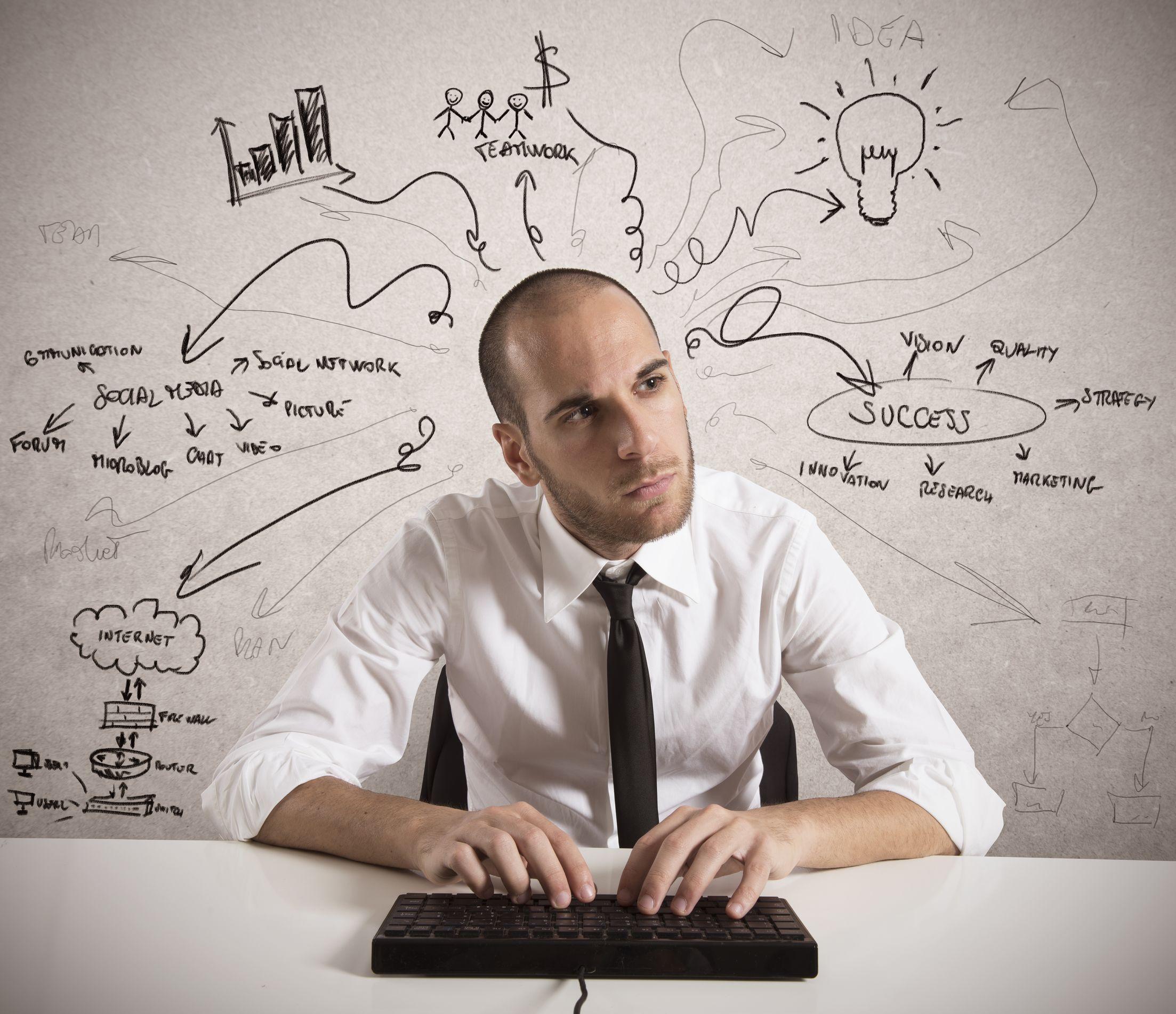 Homem de negócios escrevendo no teclado de um computador. Ao fundo, desenhos representando suas ideias.