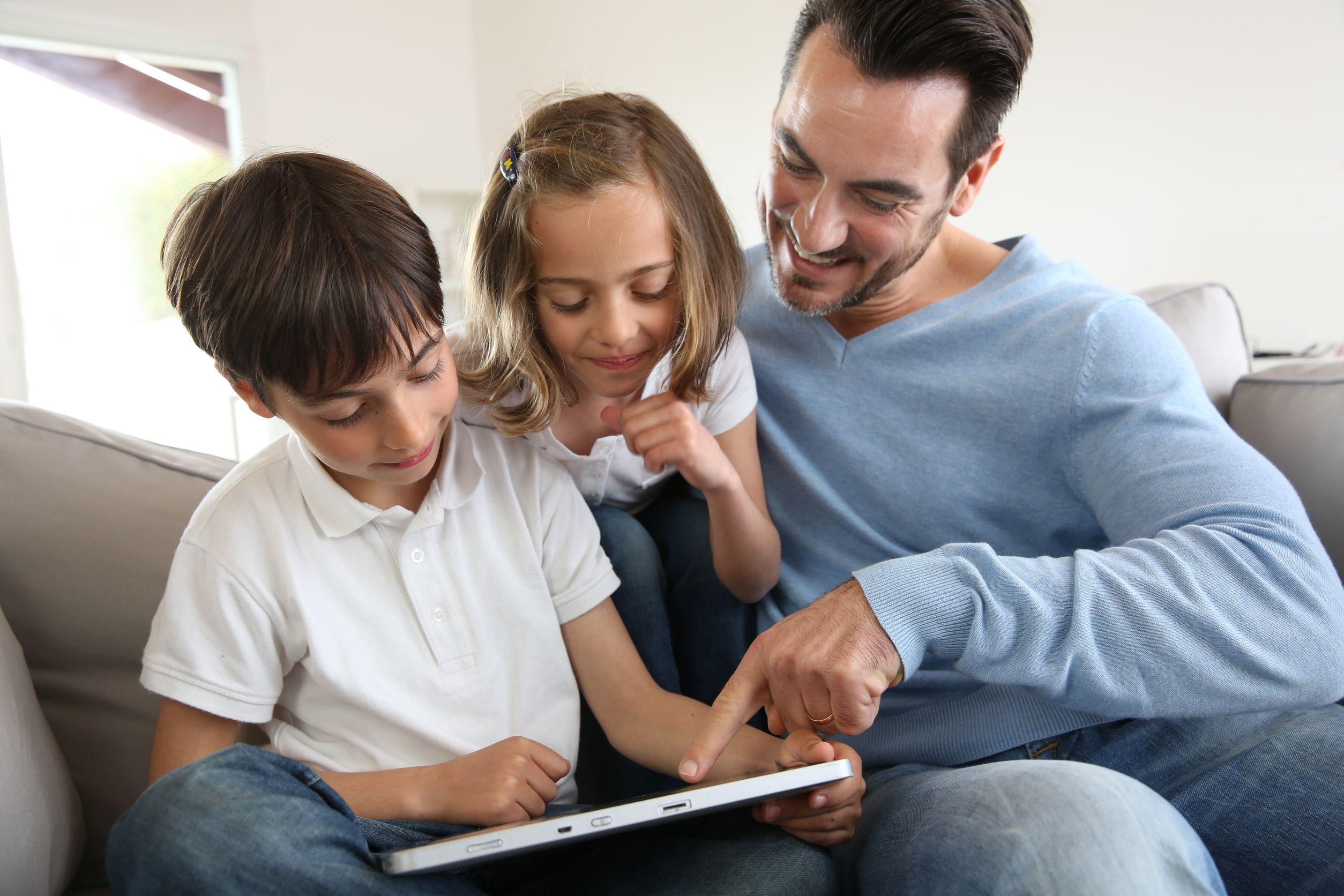 Pai e filhos sentados no sofá. Eles mexem em um tablet. Menina e menino usam camisetas brancas. Pai usa blusa azul de mangas longas.