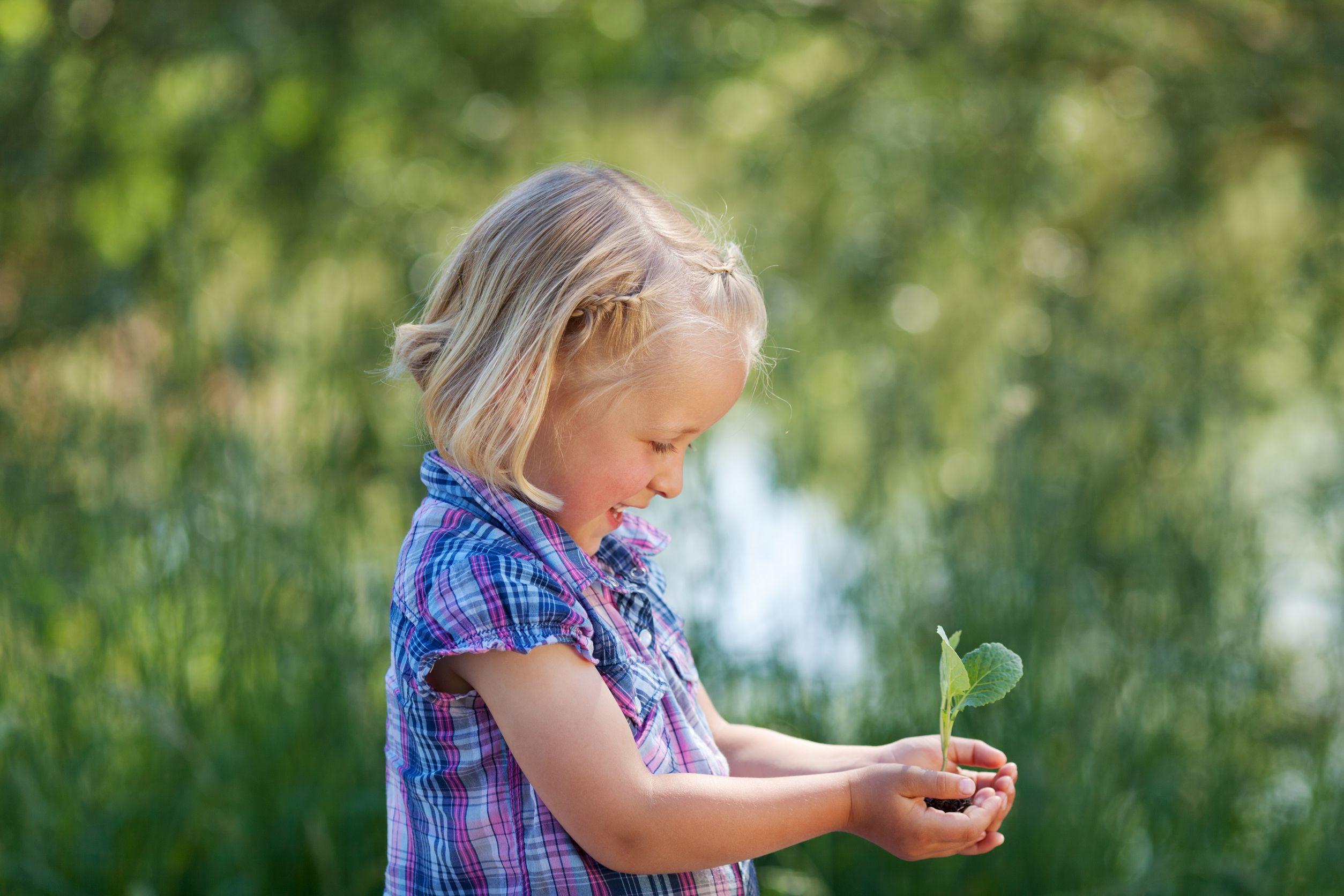 jovem alegre segurando uma planta pequena em suas mãos