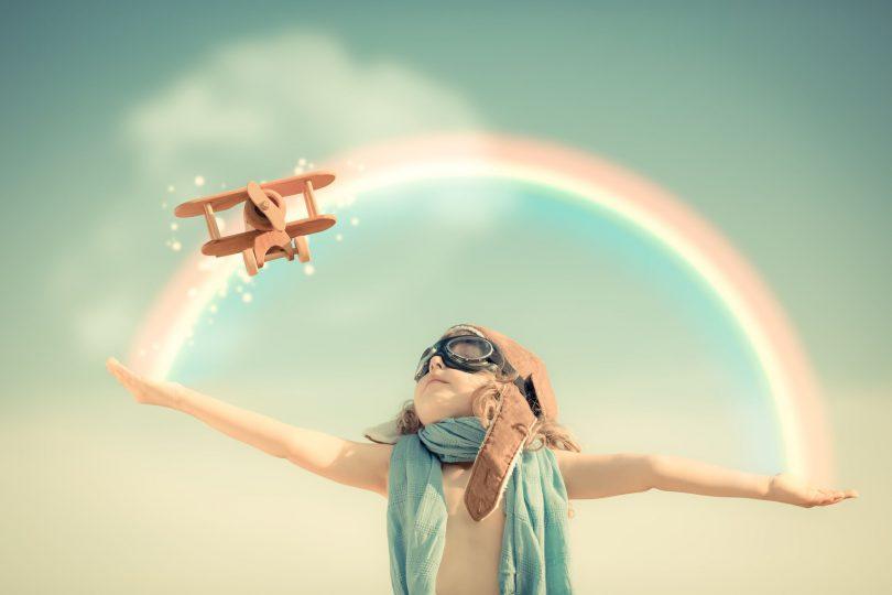 garoto feliz jogando com avião de brinquedo contra o fundo do céu de verão