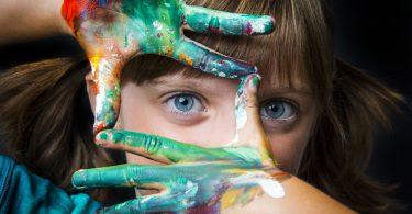 menina pequena com as mãos sujas de tintas coloridas.