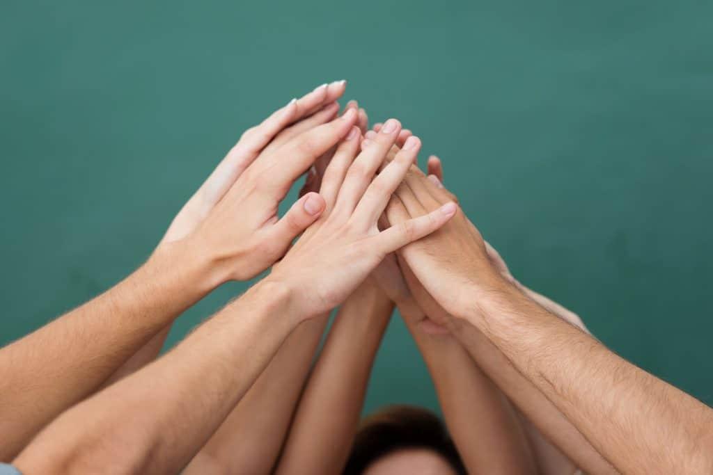 Mãos unidas formando uma espécie pirâmide.