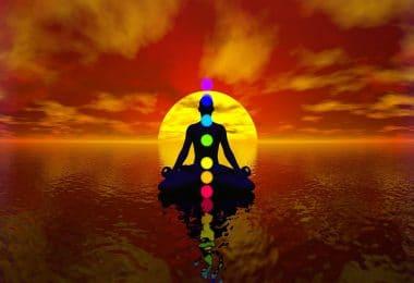 Desenho gráfico de um homem em meditação. Chakras representados como bolas coloridas. Fundo de pôr-do-sol e mar.