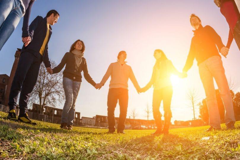 Pessoas de mãos dadas em um círculo.