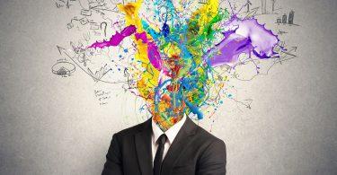 Conceito de mente criativa. Homem vestido de terno. No lugar da cabeça existe uma explosão colorida.