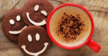 copo vermelho brilhante de espumoso café com biscoitos de chocolate com sorrisos feitos de chocolate branco.