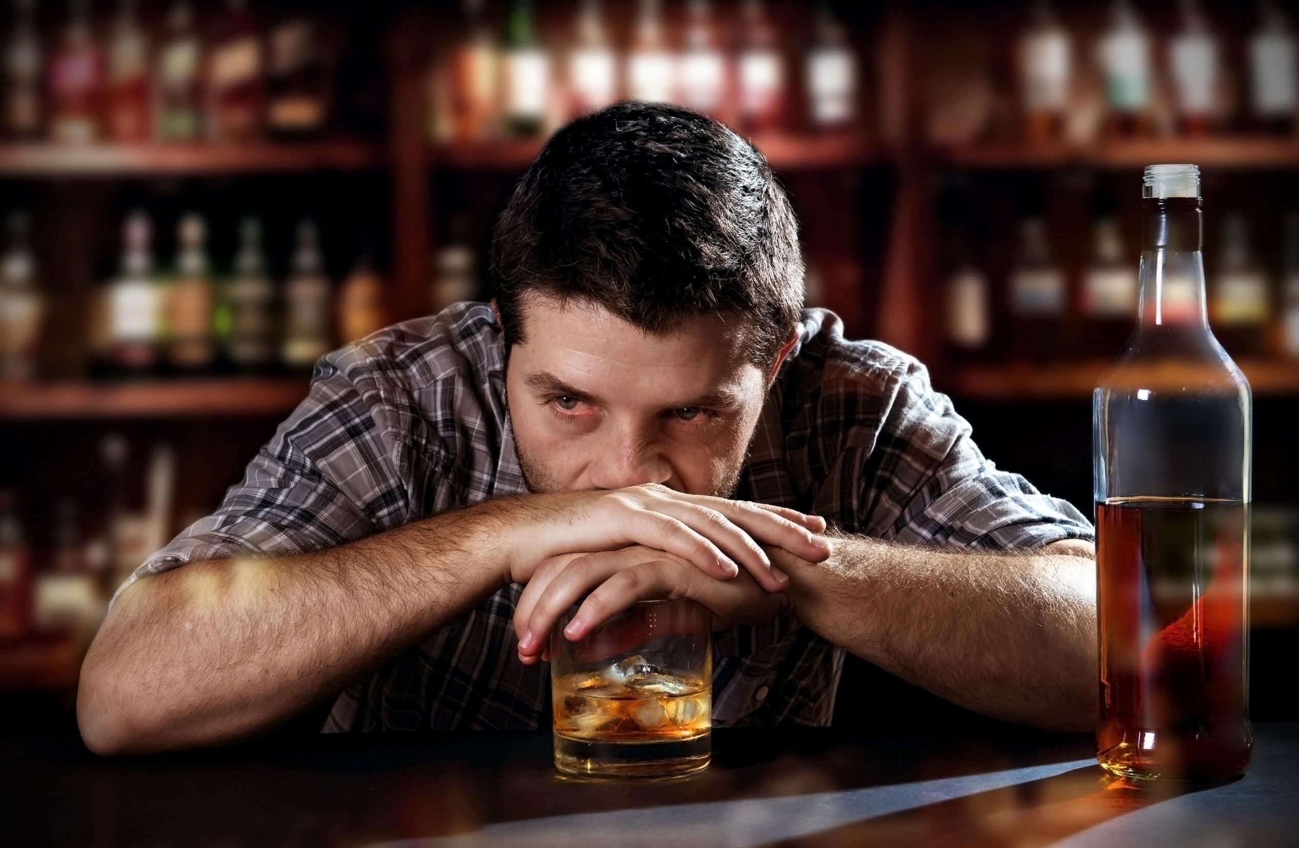 Jovem bebendo álcool pensando no vício. Está em um bar.