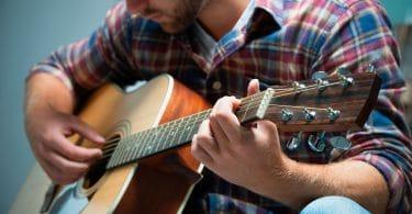 Close em um músico tocando um violão. Ele veste uma blusa xadrez.