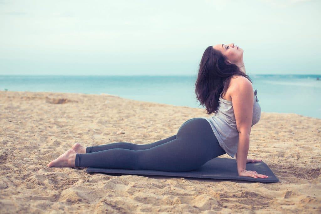 Mulher fazendo yoga em uma praia.