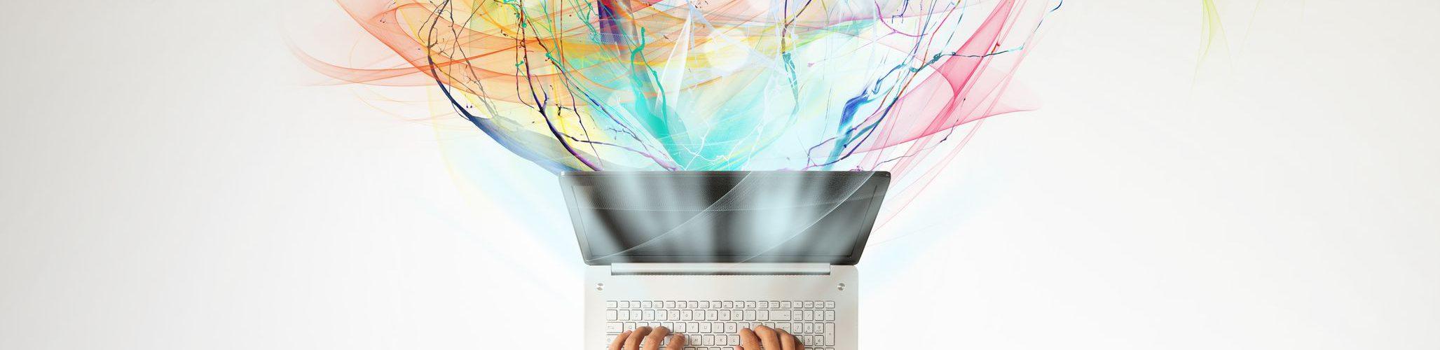Homem sentado em uma mesa branca, mexendo em notebook, que tem diversas fitas de cores diferentes ao seu redor.