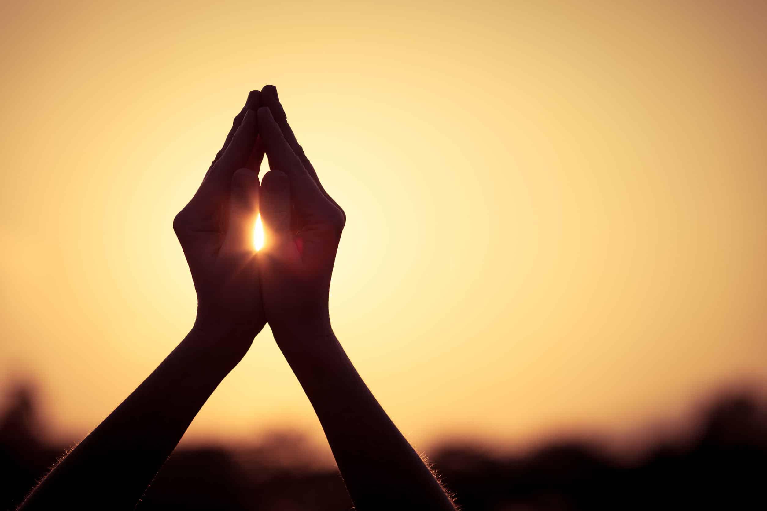 silhueta de mãos femininas durante o pôr do sol