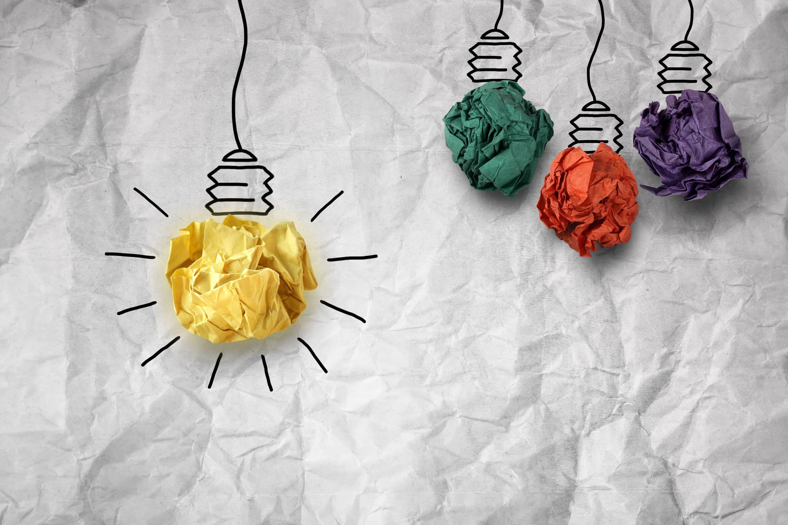 """Papéis amassados. Nas cores vermelho, roxo, verde e amarelo. Todas fazem o formato de uma lâmpada. Apenas a amarela está """"acessa""""."""