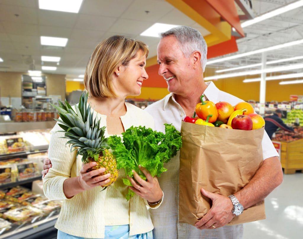 Casal adulto no supermercado segurando sacola com vegetais.