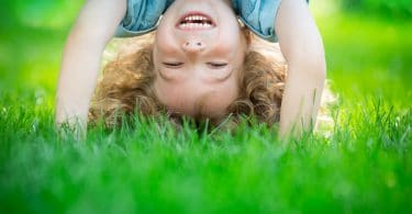 Uma criança sorridente plantando bananeira em um gramado verde. A criança é um menino de cabelos cacheados loiros.