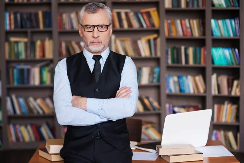 Professor em pé em biblioteca. Ele se apoia em uma mesa cheia de livros. Usa óculos e tem cabelo grisalho.