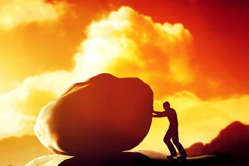 Homem empurrando uma pedra gigante e pesada, sobre a montanha.