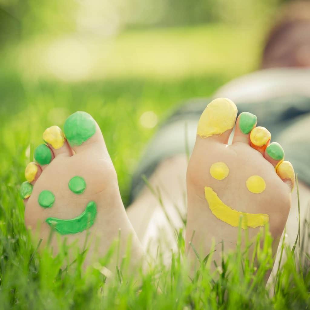 Os pés de uma criança deitada na grama. A parte de baixo dos pés está pintada de verde e amarelo e há um sorriso desenhado com tinta.