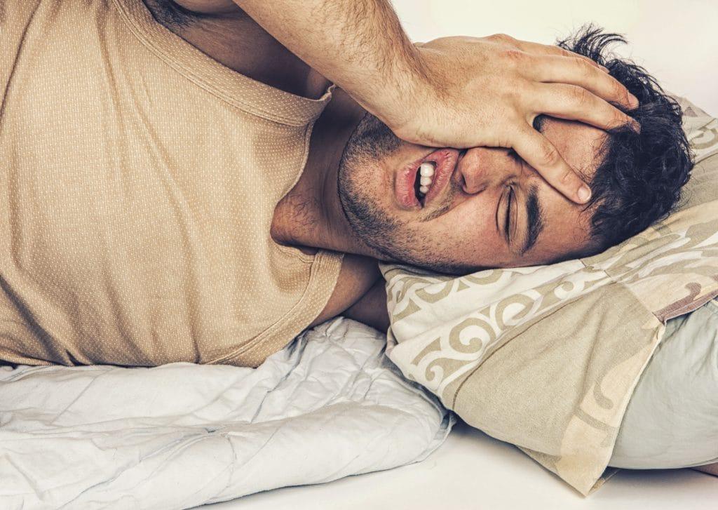 Homem deitado na cama com a mão sobre o rosto.