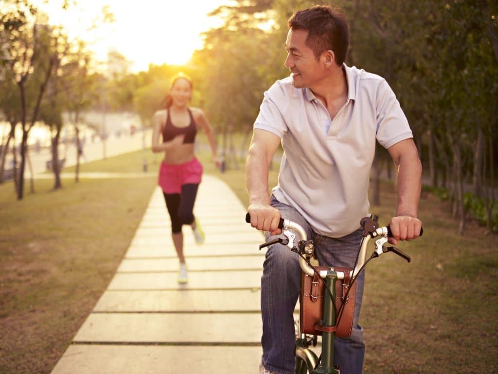 Casal asiático em um parque. A mulher está ao fundo correndo e o homem está a frente andando de bicicleta.
