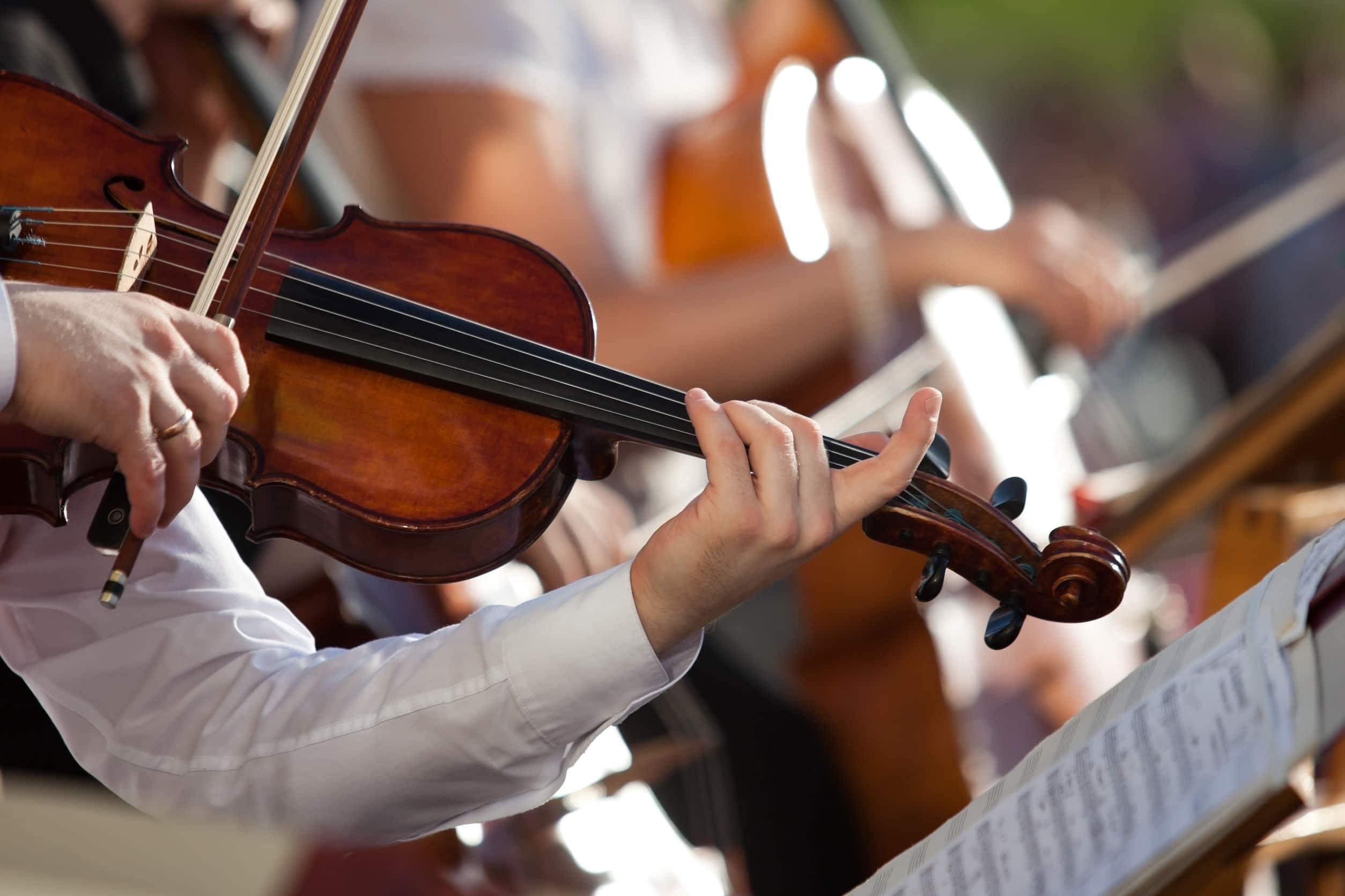 Homem tocando violino. Usa camisa branca. Ao fundo outras pessoas tocando.
