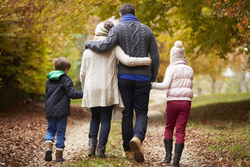 Família andando de mãos dadas em um caminho de folhas. Um menino. Uma menina. Um homem. Uma mulher. Todos usam roupas de frio.