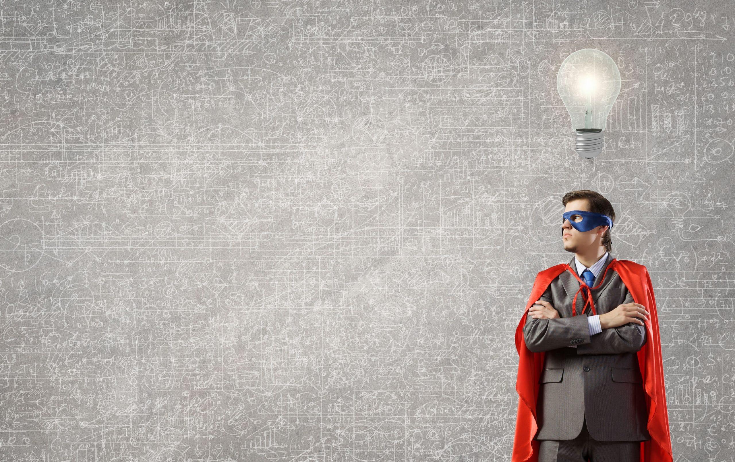Jovem usando terno vestido de super herói. Uma lâmpada acessa está acima da cabeça dele. Conceito de ideia nova. Conceito de coragem para ser criativo.