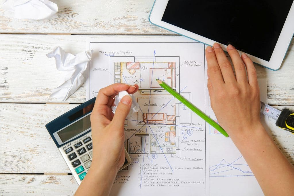 Mulher desenhando um plano de Feng Shui para uma casa. Ela está usando uma mesa e em cima da mesa há uma calculadora, um IPad e um desenho da casa.