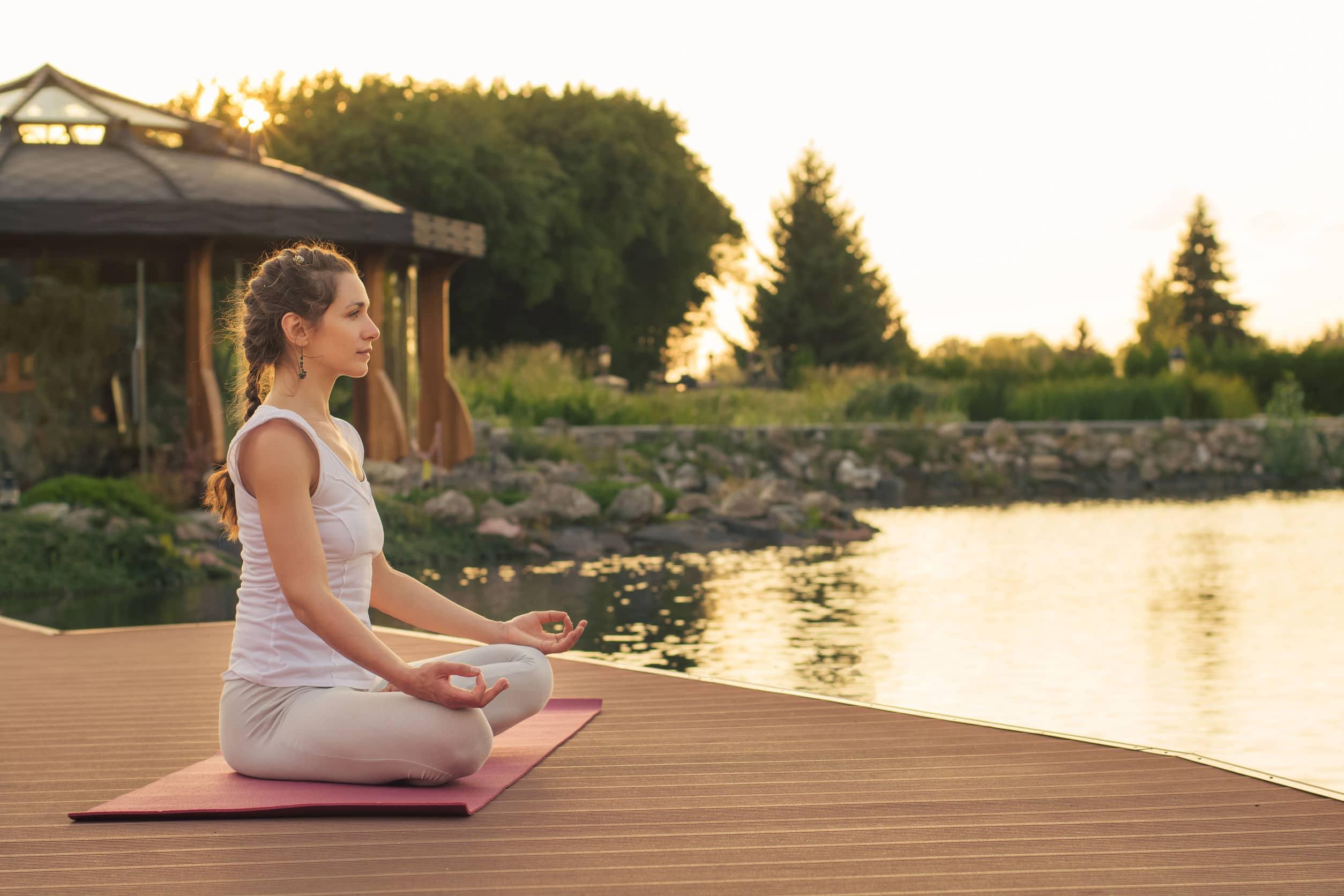 Mulher meditando perto de um lago ao pôr-do-sol.