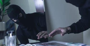 Bandido vestido um mascara de esqui preta, roubando jóias da cômoda de um quarto