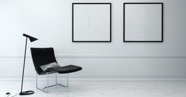 Cadeira moderna e luminária de chão em sala escassamente decorada com arte-final emoldurada minimalista pendurado na parede.