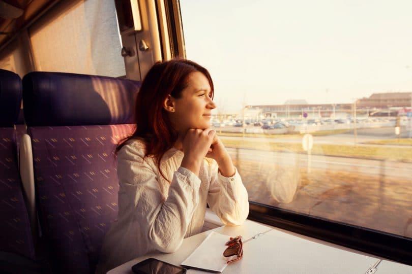 Mulher jovem sentada, viajando em trem, olhando para a janela.