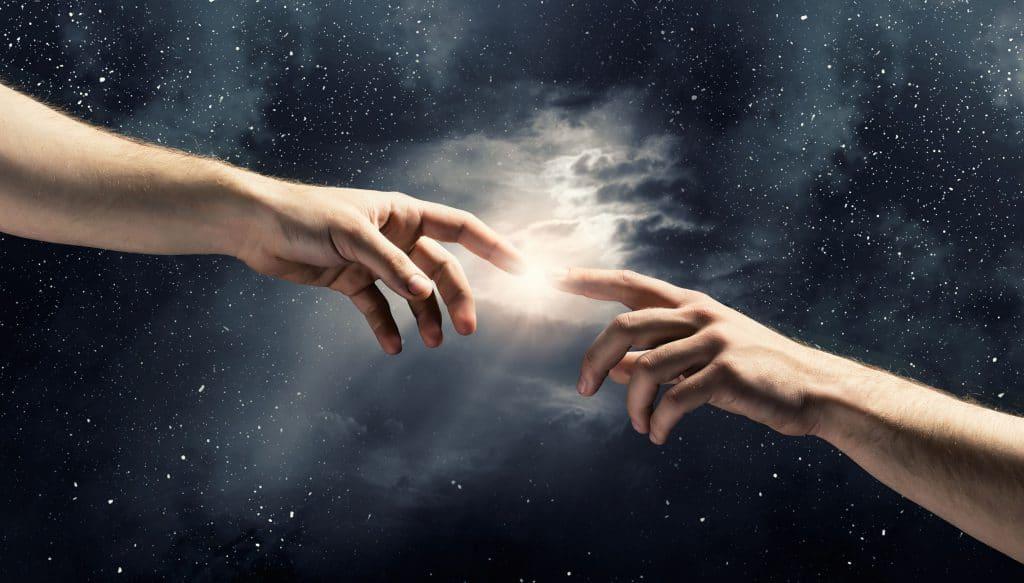 Duas mãos no espaço, com seus dedos indicadores quase se tocando. Entre os dedos, uma luz faz a ligação entre eles.