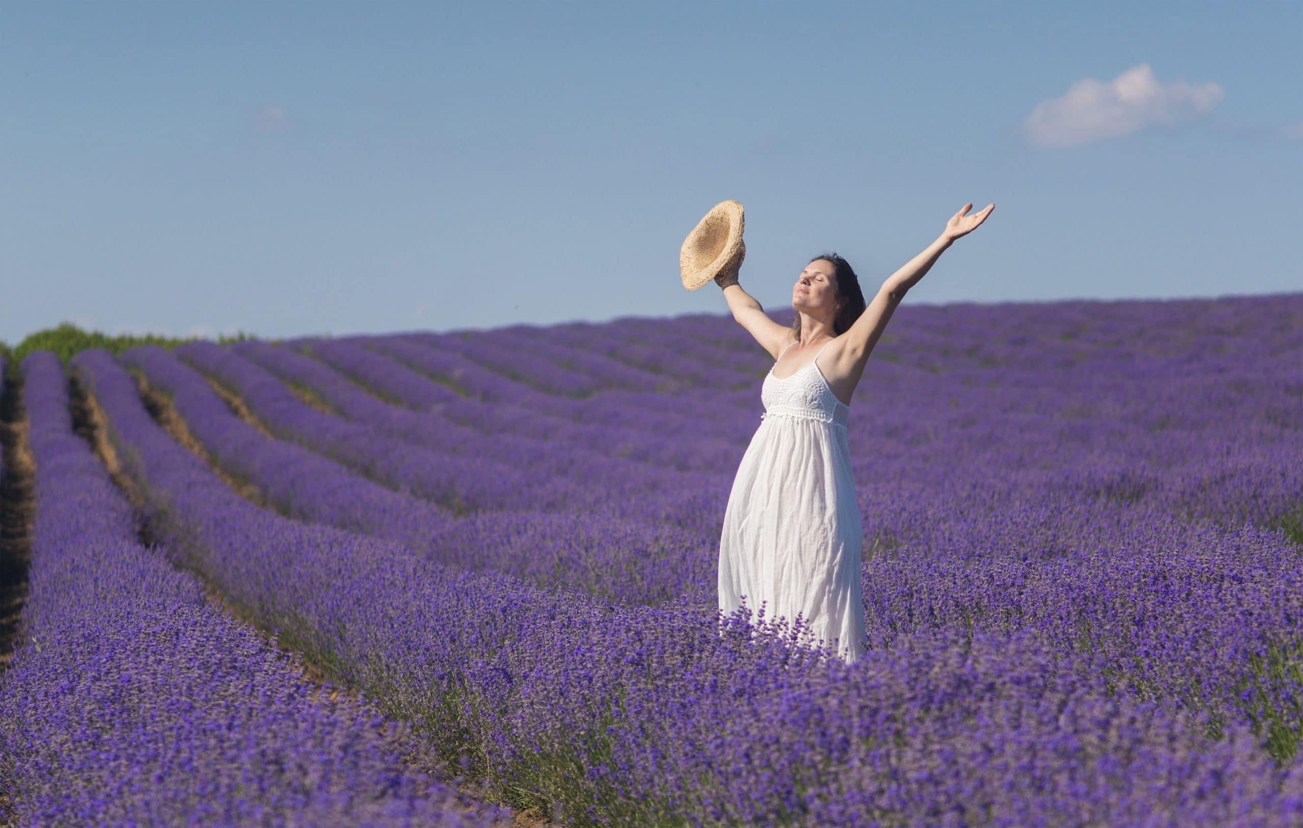 Mulher estendendo os braços. Fundo de campo. Muitas flores roxas e céu azul.