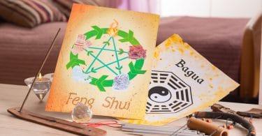 Uma mesa com dois papéis amarelados em cima. Um deles está escrito Feng Shui e há elementos desenhados nele. O outro papel está escrito Bágua e também tem símbolos desenhados nele. Além disso há alguns outros elementos como cristais.