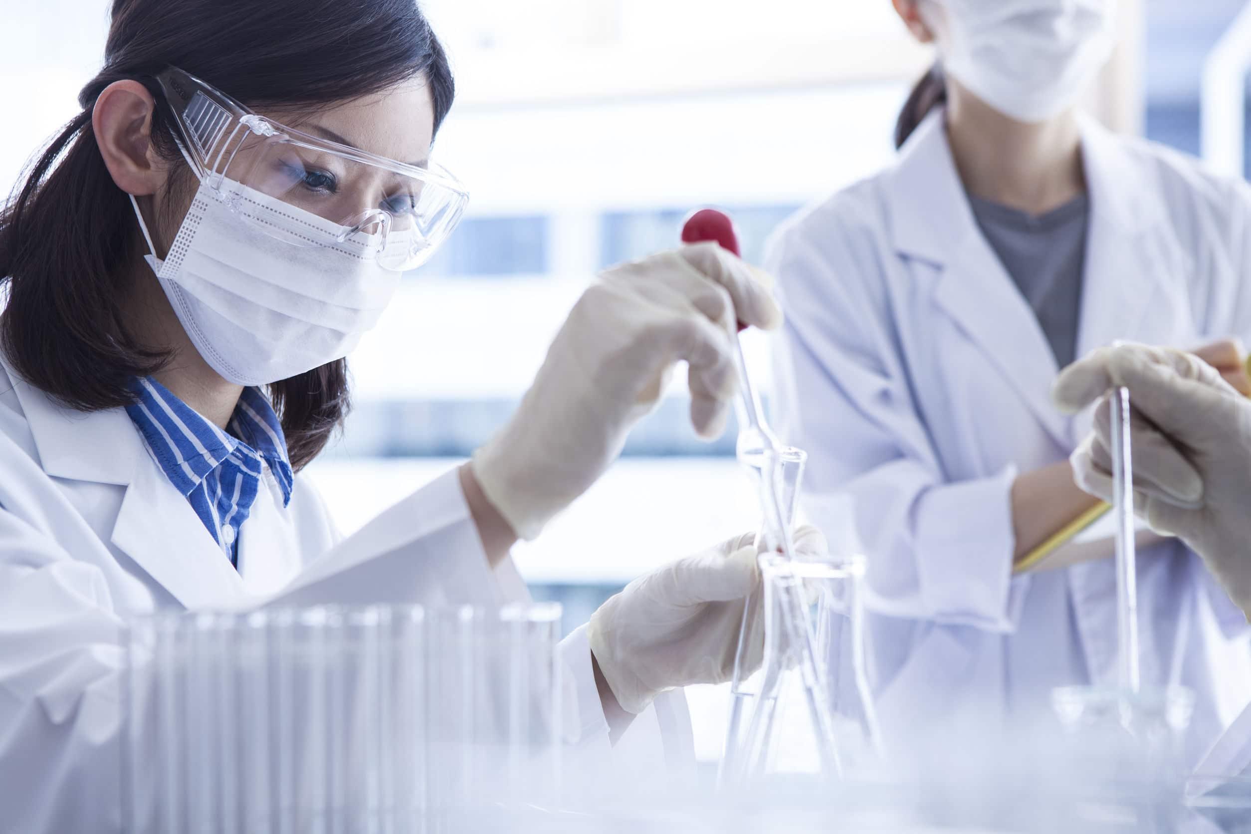 Dois cientistas trabalhando em laboratório. Todos usam branco.