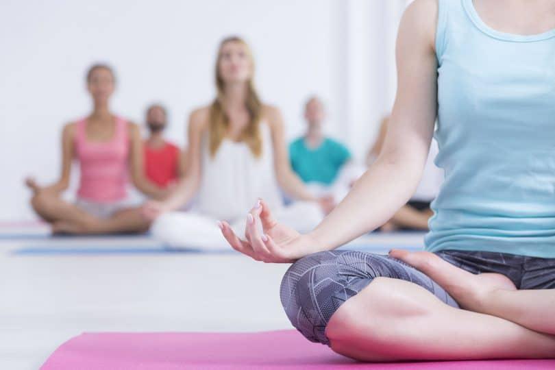 mulher vestindo roupas de ginástica, sentada em um tapete rosa e fazendo yoga