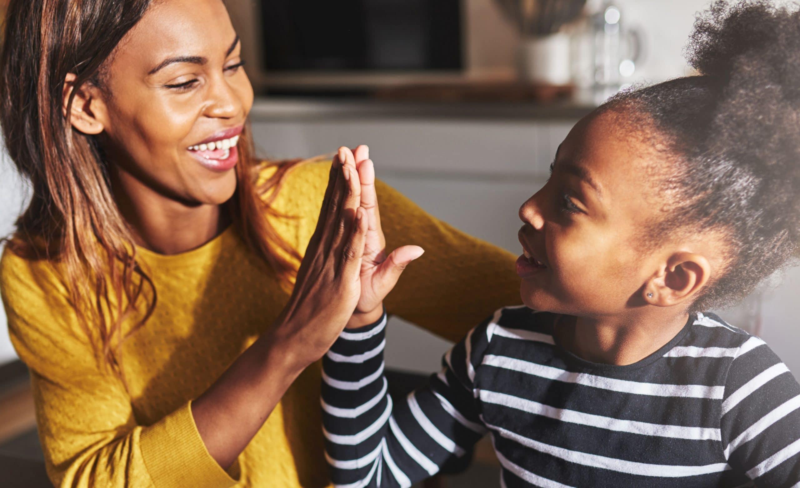 Mãe e filha batendo as mãos. Ambas negras. A mãe usa amarelo. A filha usa uma blusa listrada em preto e branco.