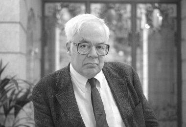 Retrato em preto e branco de Richard Rotyr. Ele está sentado em uma cadeira. Ele usa terno e gravata.