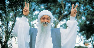 Osho, vestido de branco, fazendo o sinal da paz com as duas mãos, com árvores ao fundo.