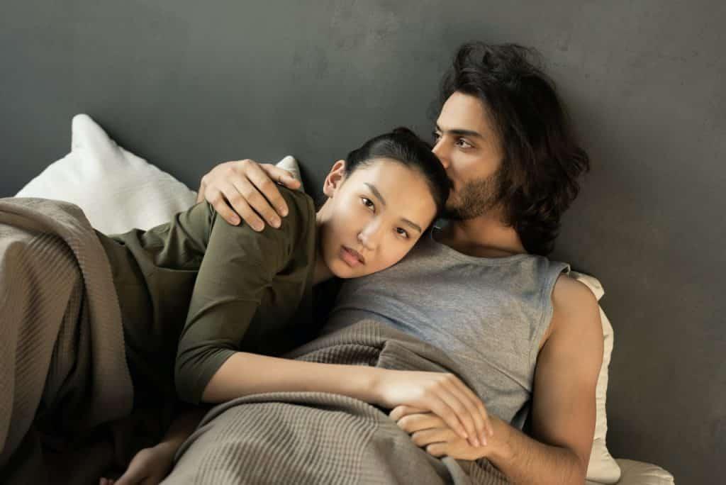 Homem e mulher deitados abraçados em uma cama.